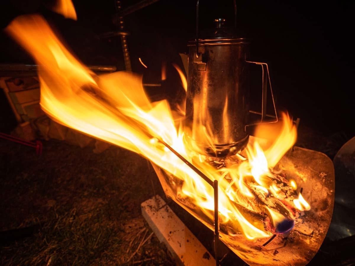 風で強くなった焚き火にかかるケトル