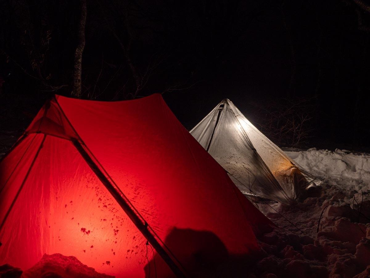 夜の雪山で光るテント