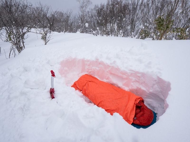 雪を掘って寝袋で寝る