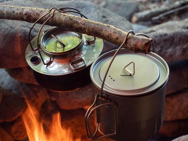 木に吊るした鍋を焚き火にかける