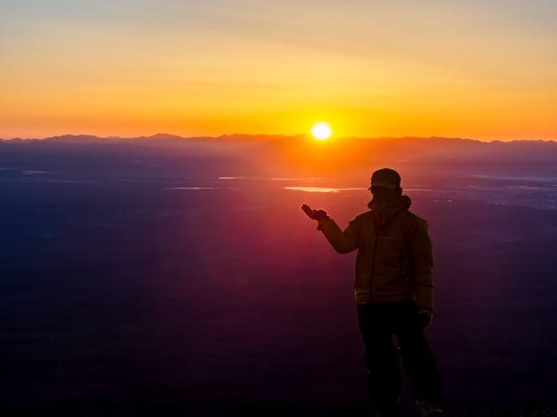日の出の太陽を手の上に乗せる