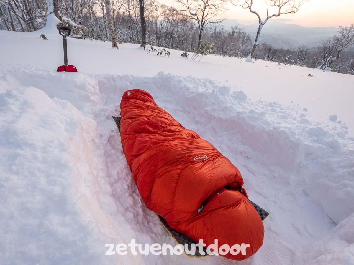 雪の上で寝袋で寝る