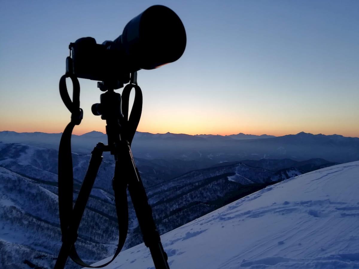 冬山でカメラを立てて日の出待ち